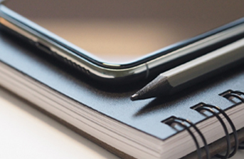 A close-up of an iPhone on a notepad
